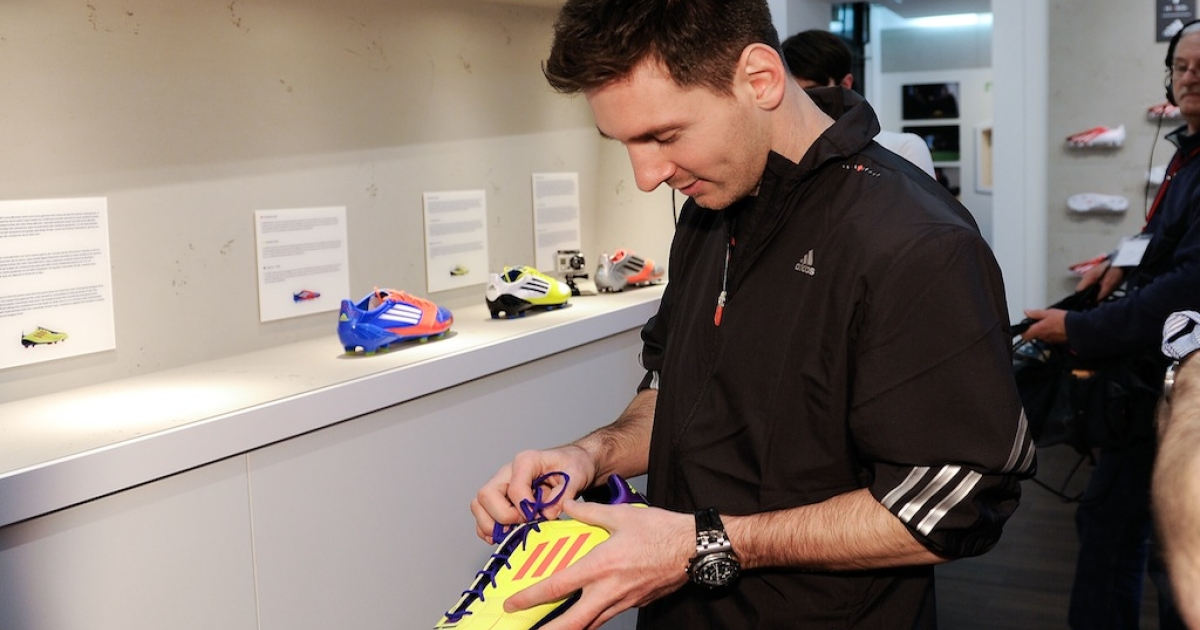 Lionel Messi checks an old f50 Messi boot during his visit to the new adidas Messi Gallery on March 6, 2013 in Barcelona, Spain.</p>
