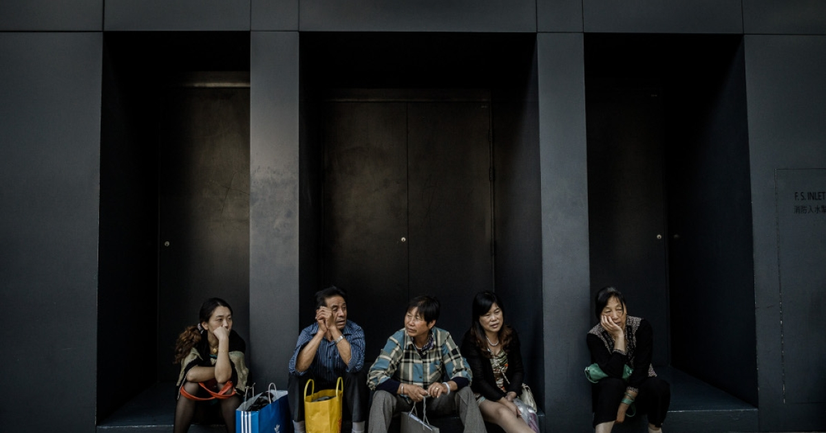 Chinese visitors from the mainland sit in front of a luxury shop in Hong Kong on September 28, 2012.</p>