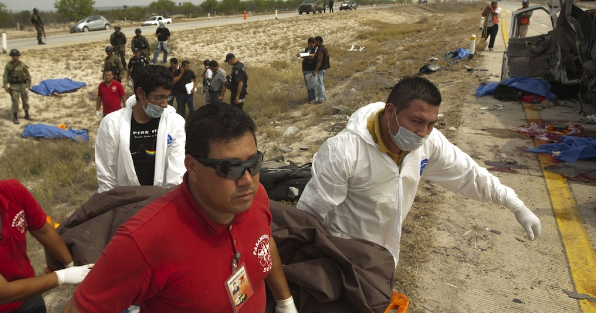 Emergency rescue workers carry the body of one of the 10 members of La Reyna de Monterrey killed in a horrific traffic accident in northern Mexico on April 27, 2013.</p>