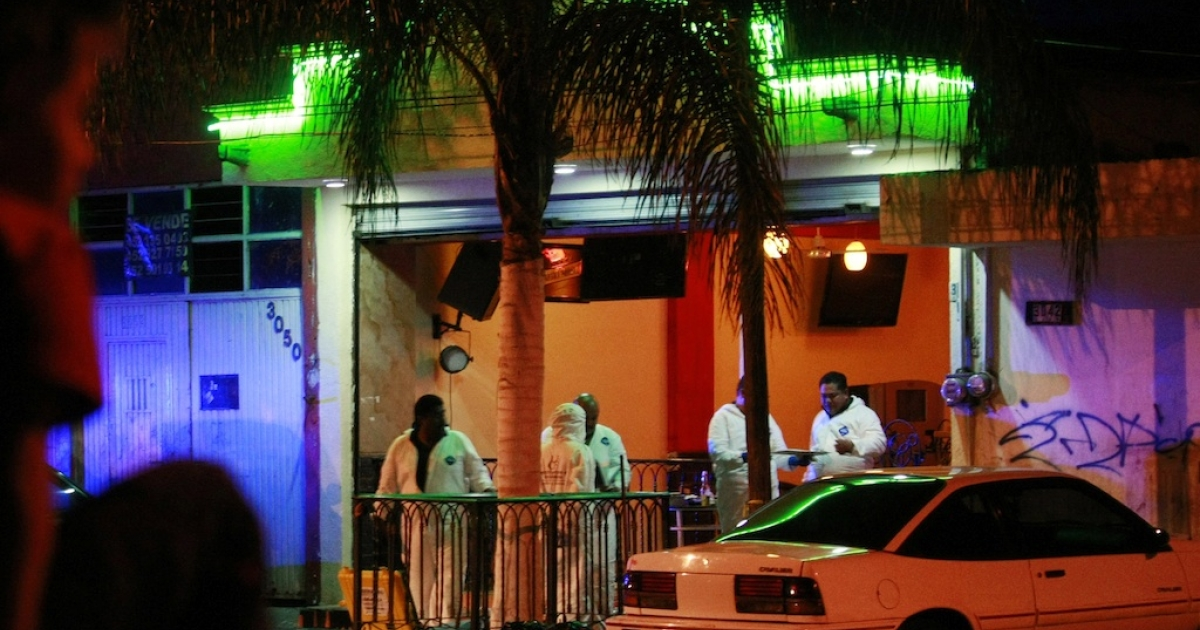 Forensic officers arrive at a bar in Guadalajara where gunmen killed two people on March 31, 2013.</p>