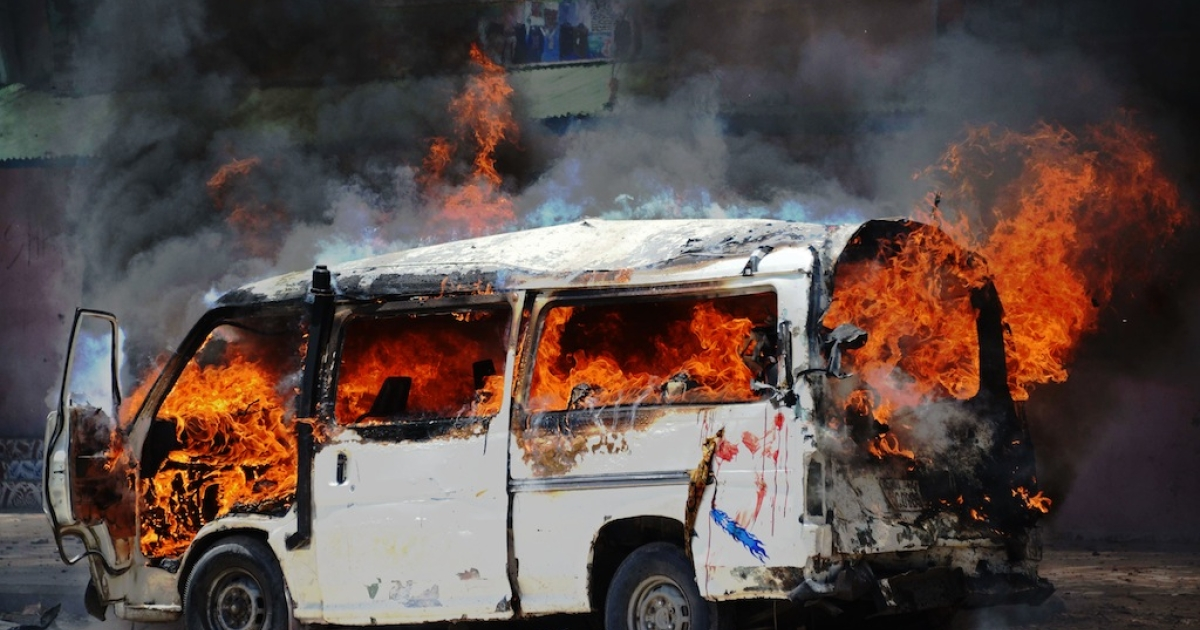 A mini-bus on fire after a car bomb explosion in Somalia's Mogadishu on March 18, 2013.</p>
