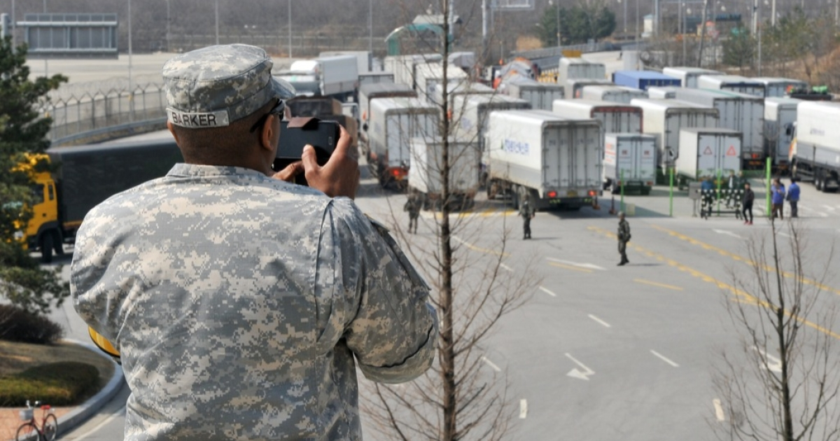 A US soldier takes pictures as South Korean trucks return after being barred access to the Kaesong joint industrial park in North Korea on April 3, 2013.</p>