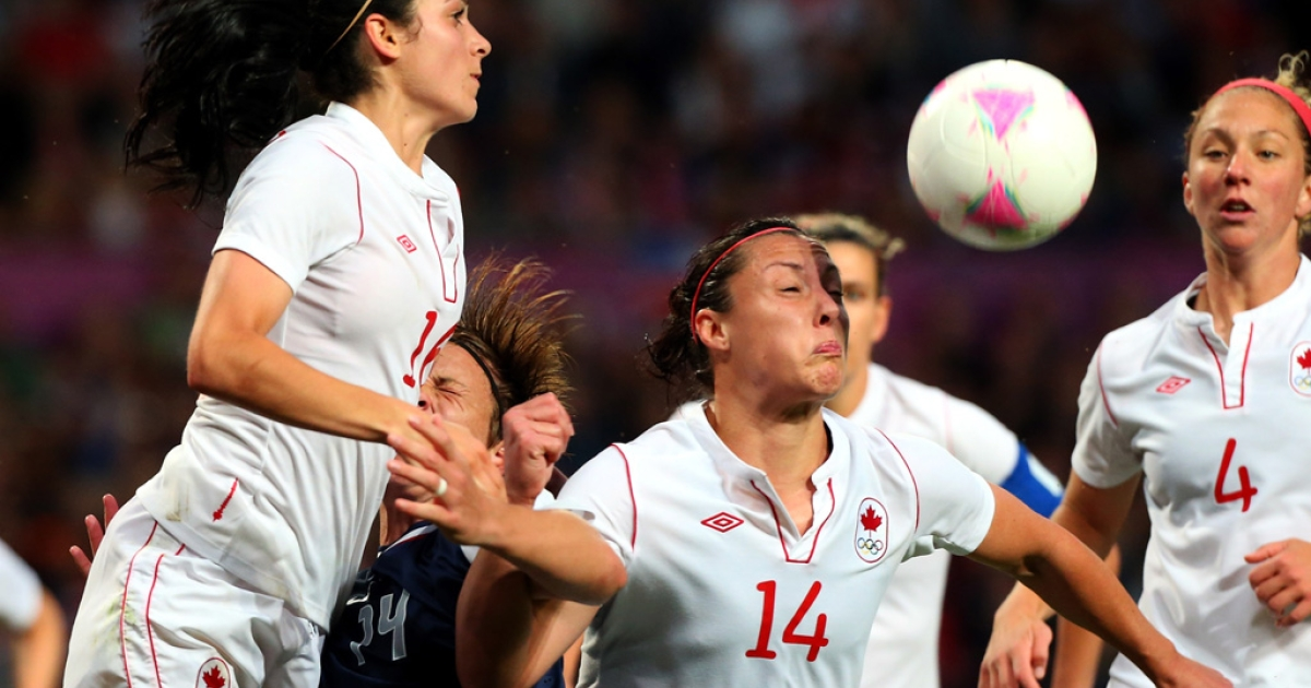 Melissa Tancredi of Canada heads the ball while Jonelie Filigno looks on during the women's soccer semifinal against the USA at the London 2012 Olympic Games at Old Trafford on August 6, 2012 in Manchester, England.</p>