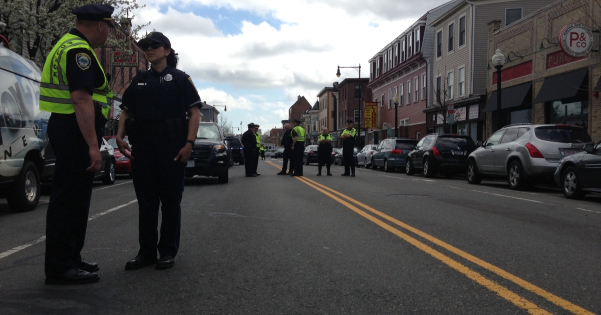 Officers stand near the intersection of Cambridge and Tremont streets on April 19, 2013 during a manhunt for a suspect in the Boston Marathon bombing.</p>
