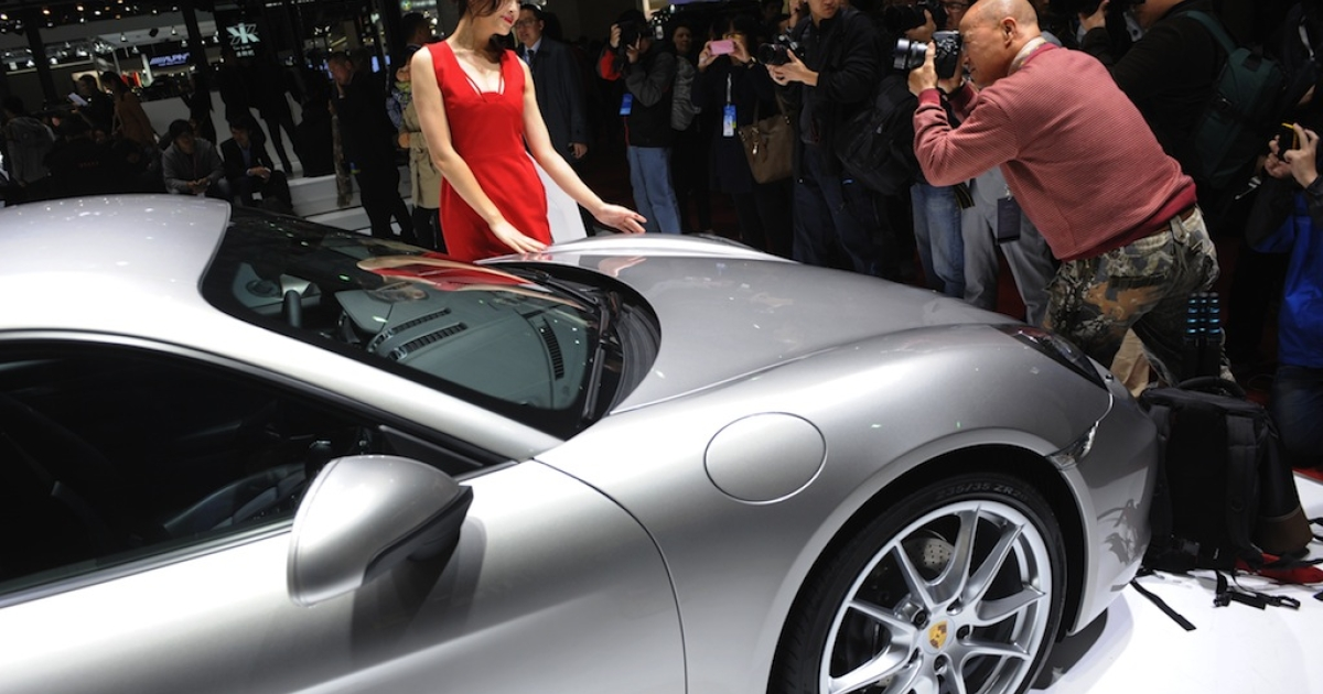 A photographer takes photos of a model next to a Porsche on media day at the Shanghai auto show on April 20, 2013.</p>
