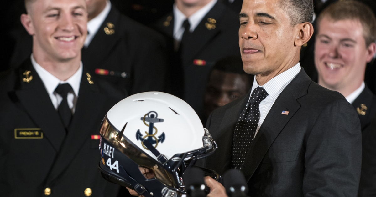 US President Barack Obama holds a Navy football helmet at the White House on April 12, 2013 in Washington, DC. Obama presented the Commander-in-Chief Trophy to the Naval Academy's football team for having the best overall record of the three US military academies.</p>