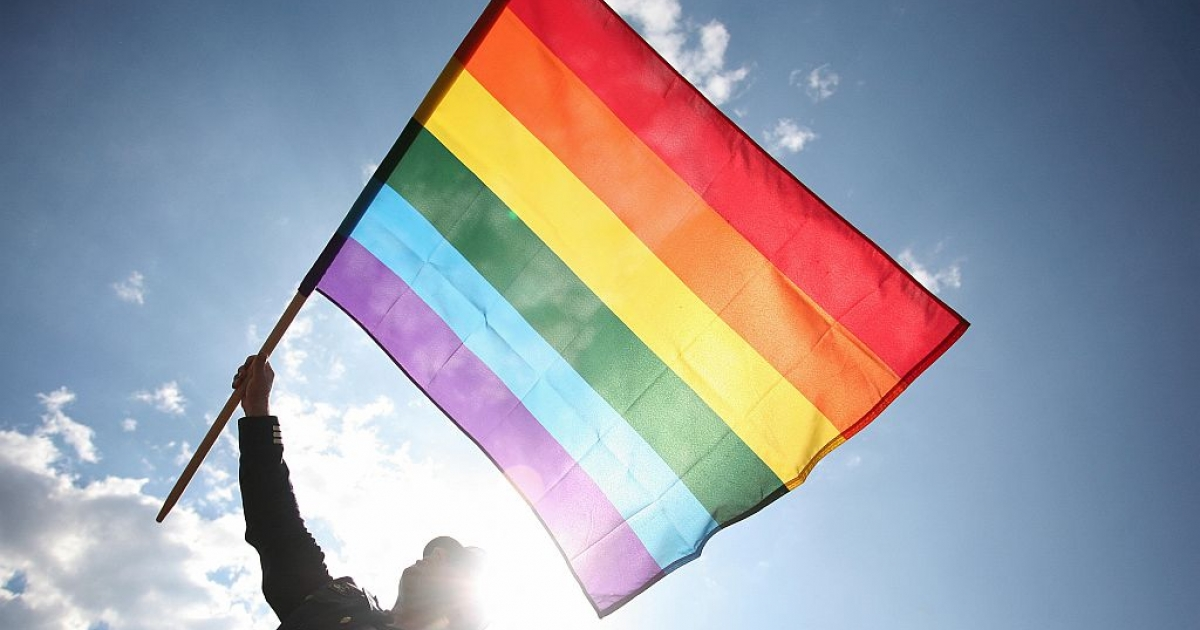 A Polish man waves a rainbow flag as he takes part in Warsaw's Gay Pride parade on June 7, 2008. (WOJTEK RADWANSKI/AFP/Getty Images)</p>