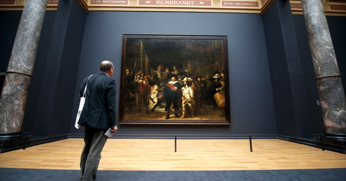 A visitor admires Rembrandt's masterpiece 'The Night Watch' at Amsterdam's Rijksmuseum, home to the world's finest collection of Golden Age art, at a press preview on April 4, 2013.</p>