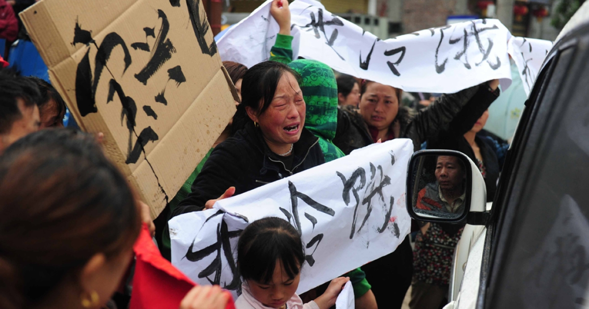 Residents in Lingguan township of Baoxing county gather on April 23, 2013, with banners saying