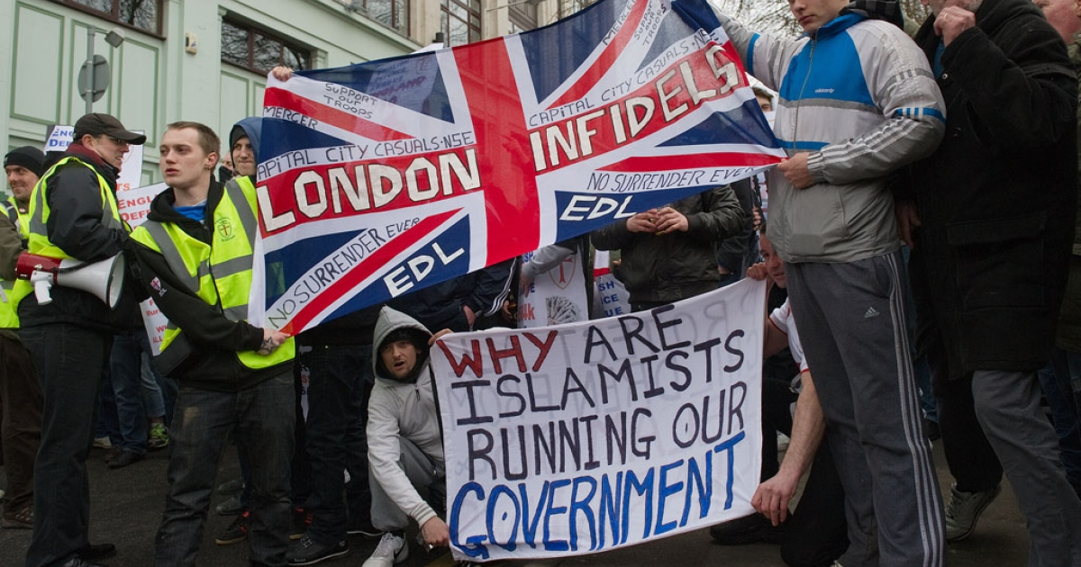 Protestors hold up flags ahead of a rally by the right-wing EDL (English Defence League) in Luton, Hertfordshire, on February 5, 2011. Six would-be terrorists pled guilty on April 30, 2013, to planning to bomb an EDL rally last year.</p>
