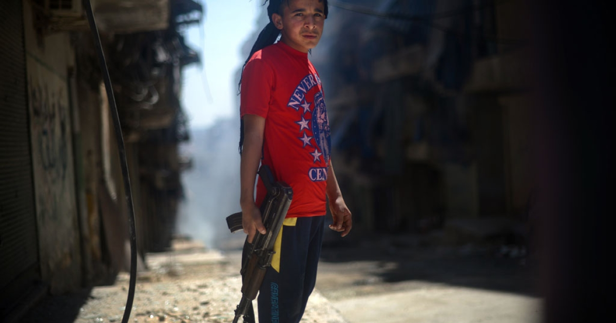 A Syrian boy holds an AK-47 assault rifle in the majority-Kurdish Sheikh Maqsud district of the northern Syrian city of Aleppo. US intelligence agencies determined with