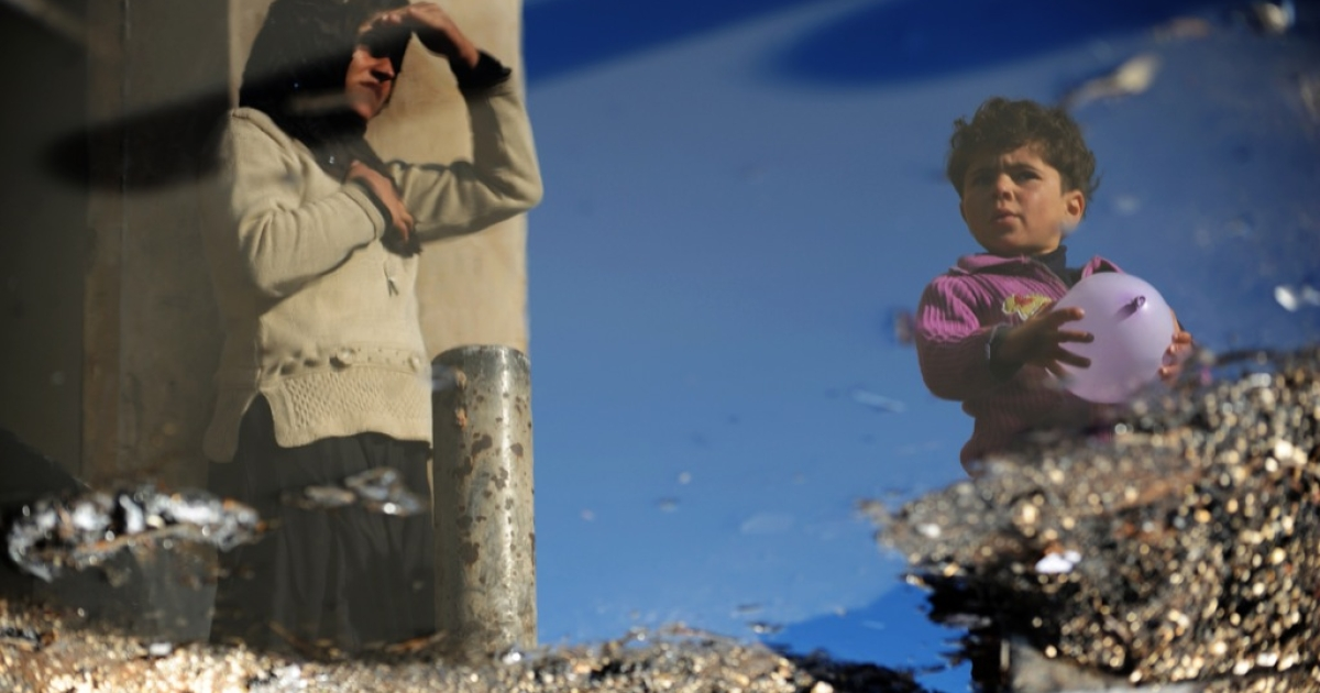 A Syrian internally displaced woman and child are reflected in a puddle of water in the Bab al-Hawa camp along the Turkish border in the northwestern Syrian province of Idlib, on March 18, 2013.</p>