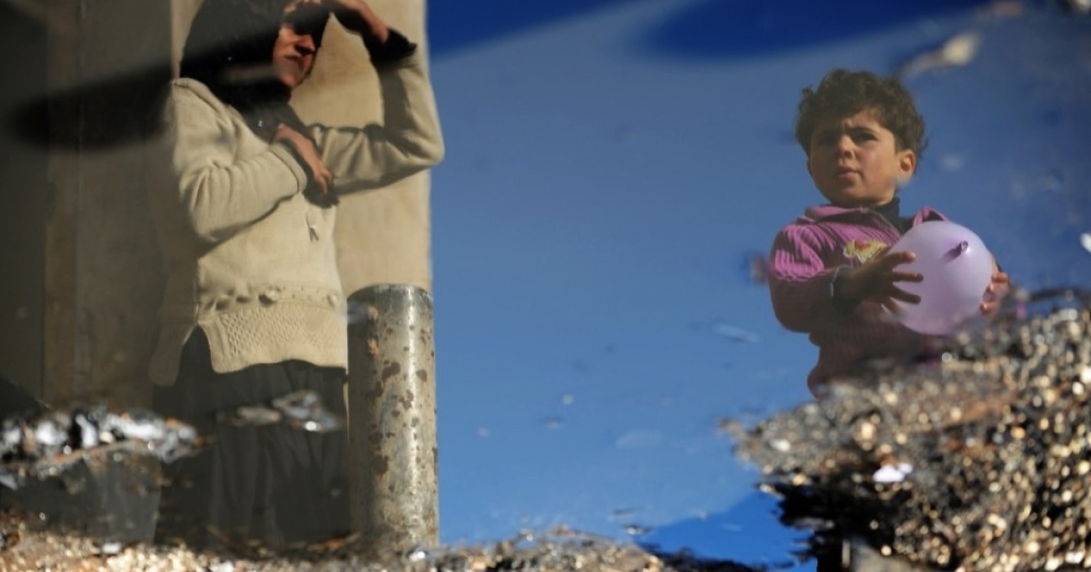 An internally displaced woman and child reflected in a puddle of water along the Turkish border in Idlib Province. Many women say they've lost their husbands' support.</p>