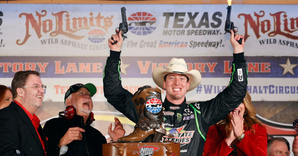 Kyle Busch, driver of the #18 Interstate Batteries Toyota, celebrates by shooting revolvers in Victory Lane as Texas Motor Speedway president Eddie Gossage (L) looks on after winning the NASCAR Sprint Cup Series NRA 500 at Texas Motor Speedway on April 13, 2013 in Fort Worth, Texas.</p>