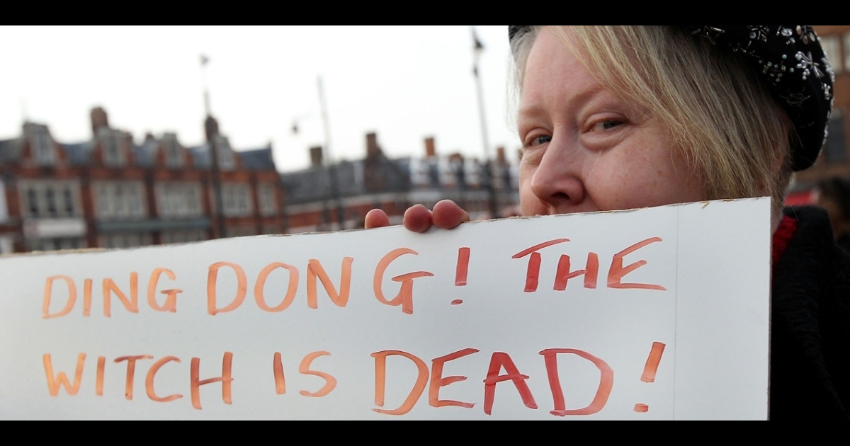 A woman poses next to a sign displaying the message 'Ding Dong! The Witch is Dead!' as she celebrates the death of former British Prime Minister Margaret Thatcher on April 8, 2013 in London, England.</p>