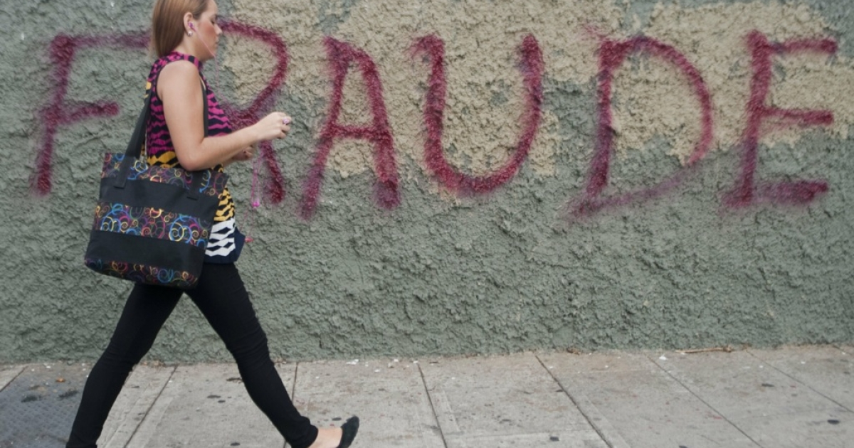 A woman walks past a message painted on a wall in the streets of Caracas reading 'Fraud' as a protest against Venezuelan President Nicolas Maduro and the election result which gave him as the victor, on April 17, 2013.</p>