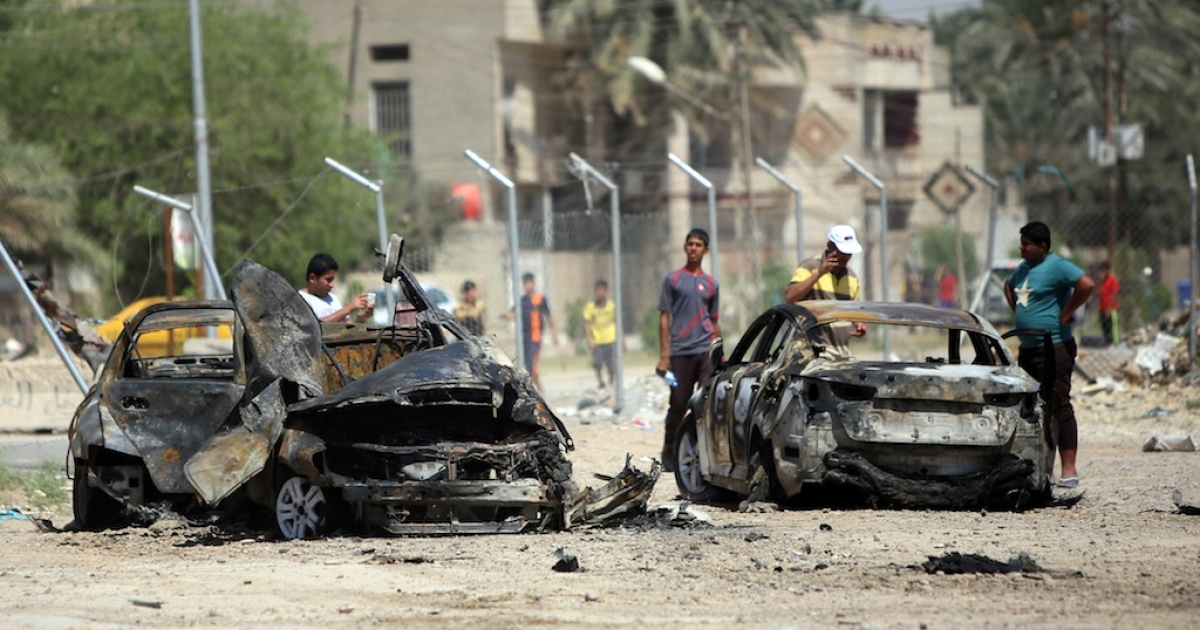 Iraqis inspect the scene of a car bomb attack near the office of Al-Ahad television channel, which is affiliated with a Shiite militant group, in Baghdad's eastern neighbourhood of Baladiyat on August 15, 2013.</p>