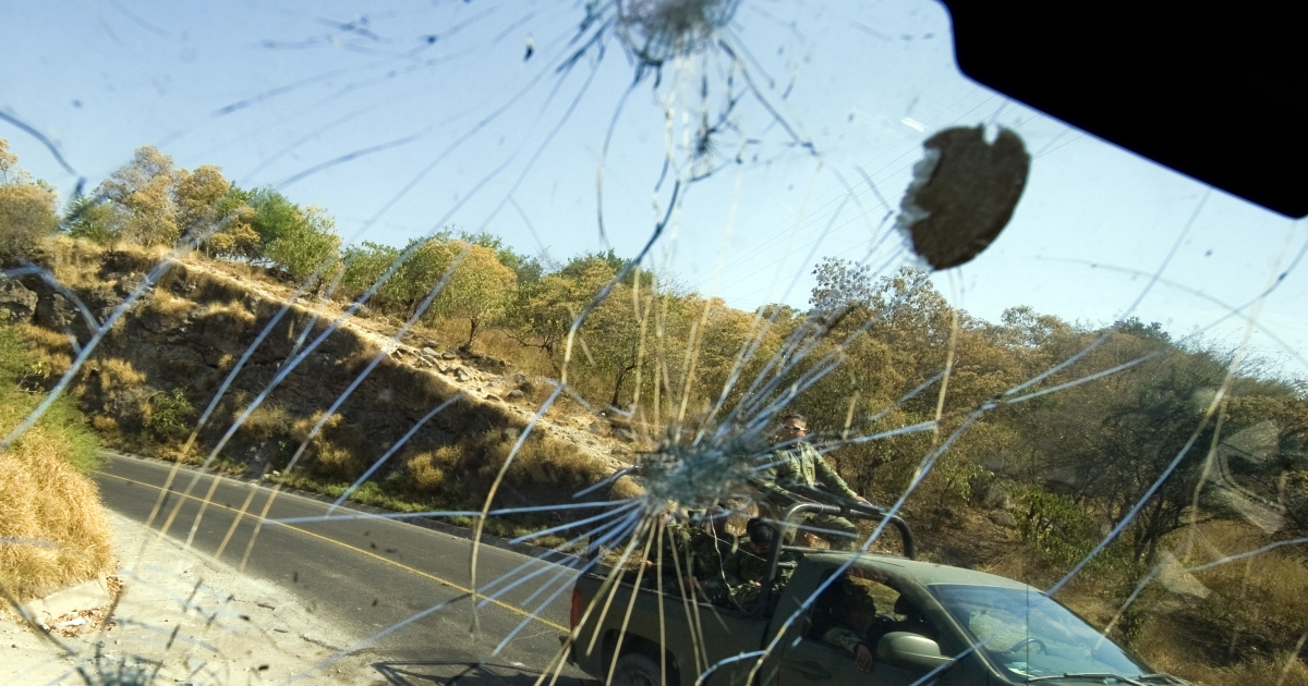 Mexican Army soldiers passing by are seen through the bullet-riddled windshield of a truck in Apatzingan, Michoacan State, on December 12, 2010. Tens of thousands of soldiers have been deployed to wage war on the country's powerful drug cartels.</p>