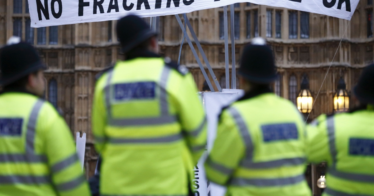 British police secure the area where demonstrators erected a mock fracking rig with a banner reading 'No fracking in the UK' in a protest against hydraulic fracturing for shale gas outside the Houses of Parliament in London on December 1, 2012. UK Prime Minister David Cameron has come out in favor of fracking in the UK.</p>
