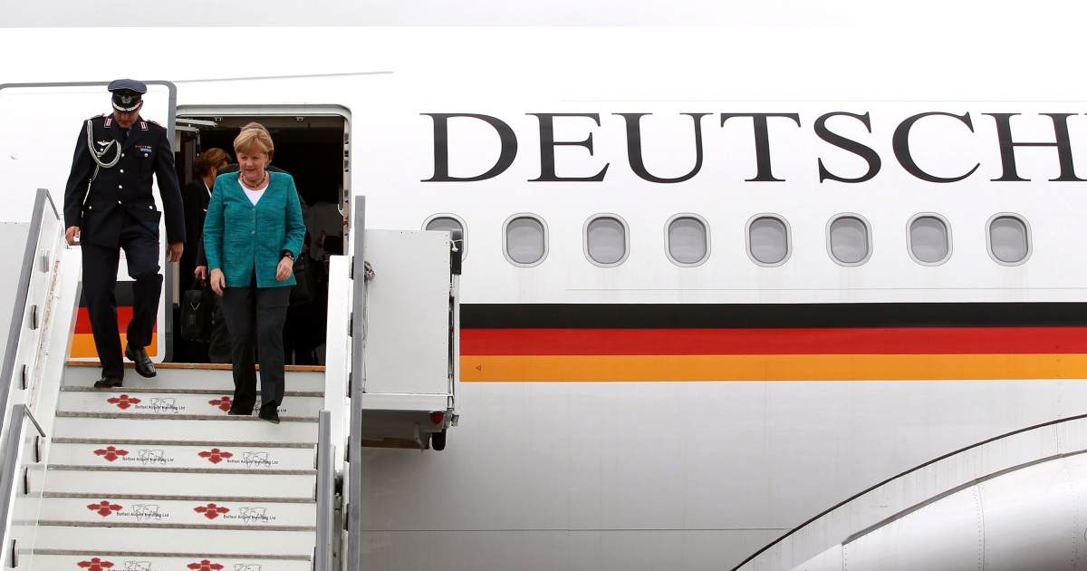 German Chancellor Angela Merkel (R) disembarks from a plane as she arrives at Belfast International airport in Belfast, Northern Ireland, on June 17, 2013, to attend the G8 summit at the Lough Erne resort. AFP PHOTO/POOL/ PETER MUHLY</p>