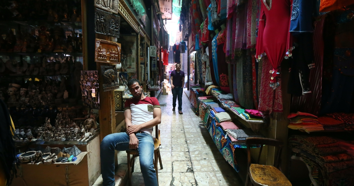 Egyptians wait for customers in an alley of the historic Khan al-Khalil market in downtown Cairo on July 13, 2013. The usually busy market place and a haven for foreigners is almost deserted.</p>