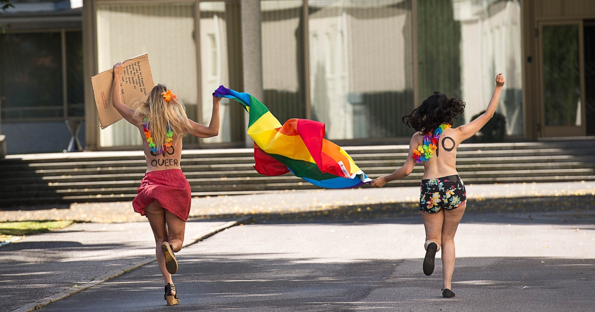 August 1, 2013- Two topless Femen activists run as they hold up a rainbow flag and a sign saying: