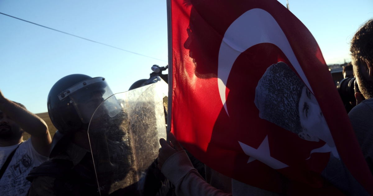 Turkish protestors wait holding a Turkish national flag on August 5, 2013 while police block ways to a courthouse in Silivri, near Istanbul, where prosecutors were scheduled to deliver their final arguments in the case against 275 people accused of plotting to overturn the Islamic-leaning government.</p>