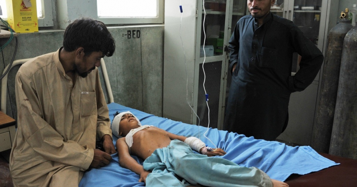 A wounded Afghan boy receives treatment at a hospital in Jalalabad after an explosion in the Ghani Khel district of Nangarhar province on August 8, 2013. An explosion killed at least 14 people in a graveyard in eastern Afghanistan on August 8, officials said, as the country celebrated the Eid al-Fitr holiday marking the end of Ramadan.</p>