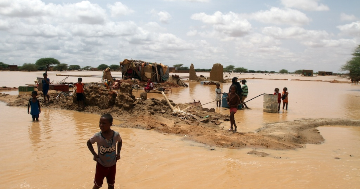 Sudanese children walks through a flooded street next to their home on the outskirts of the capital Khartoum on August 10, 2013. Drainage is poor in the capital, where even a little rain can cause flooding but this year's water surge was unusually severe.</p>