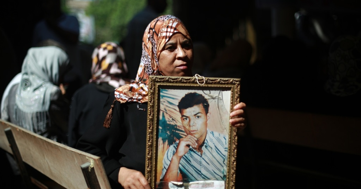 A Palestinian woman sits holding a picture of a relative during a gathering outside the Red Cross office in Gaza City on August 12, 2013. Israel has announced it will release 26 veteran Palestinian prisoners ahead of a resumption of peace talks on Wednesday.</p>