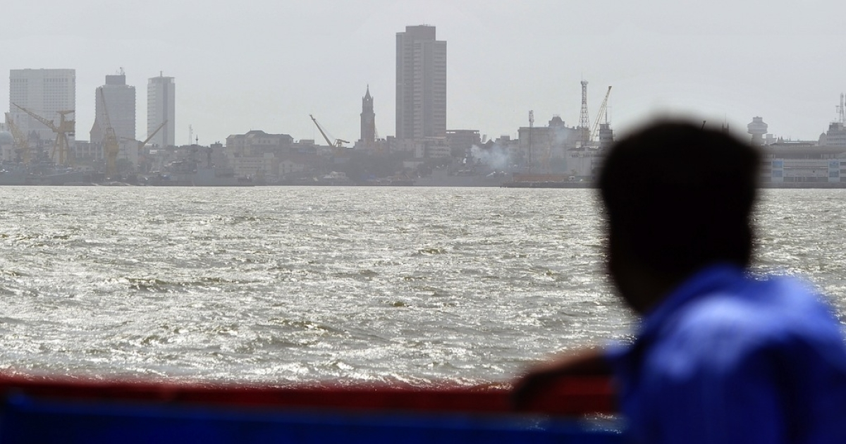 A tourist looks on from a boat as exhaust smoke rises from an Indian Navy vessel at the Naval Dockyard, the site where an Indian submarine exploded and sank, in Mumbai on August 14, 2013.</p>