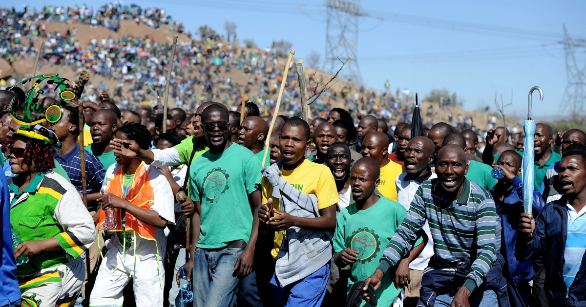 Co-workers and relatives of 34 miners shot dead by South African police during a violent wage strike sing and dance as they gather on August 16, 2013 in Marikana to mark the first anniversary of their deaths. The day marked a year after police opened fire on thousands of strikers at platinum producer Lonmin's mine, northwest of Johannesburg.</p>