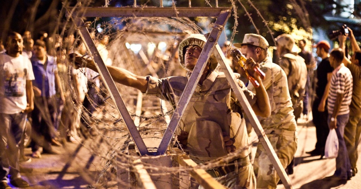 Egyptian soldiers take out barbed wire that was surrounding the Supreme Constitutional Court in Cairo ahead of planned demonstrations on August 18, 2013.</p>