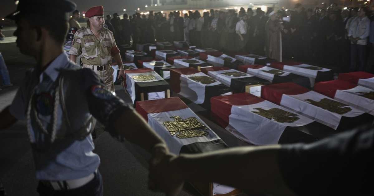 Egyptian army surround coffins covered with the national flags at Almaza military airbase in Cairo on on August 19, 2013, during a funeral for 25 policemen who were killed near the border town of Rafah, North Sinai.</p>