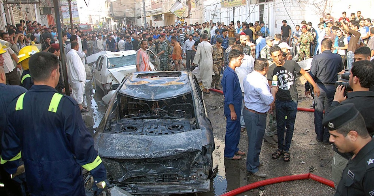 A picture taken on August 19, 2013 shows Iraqis gathering near the remains of vehicles at the scene of a car bomb explosion in Nasiriyah, south of the Iraqi capital Baghdad.</p>