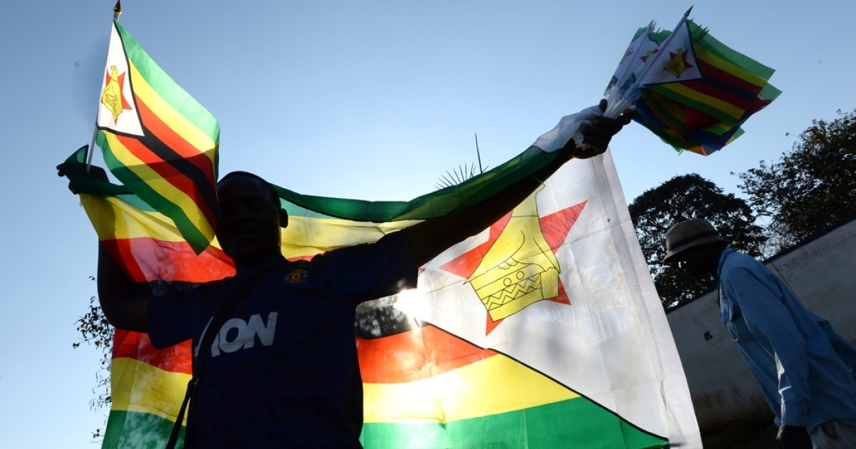 A vendor sells flags in a street in Harare on August 21, 2013, on the eve of Zimbabwean President's inauguration ceremony. President Robert Mugabe's swearing-in will be held at The National 60,000-seat sports stadium on August 22.</p>
