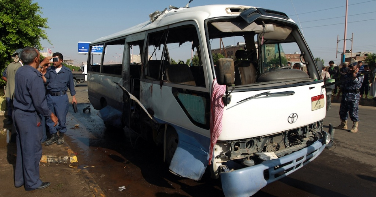 Yemeni security forces inspect a damaged military bus following a bomb blast in Sanaa on August 25, 2013.</p>
