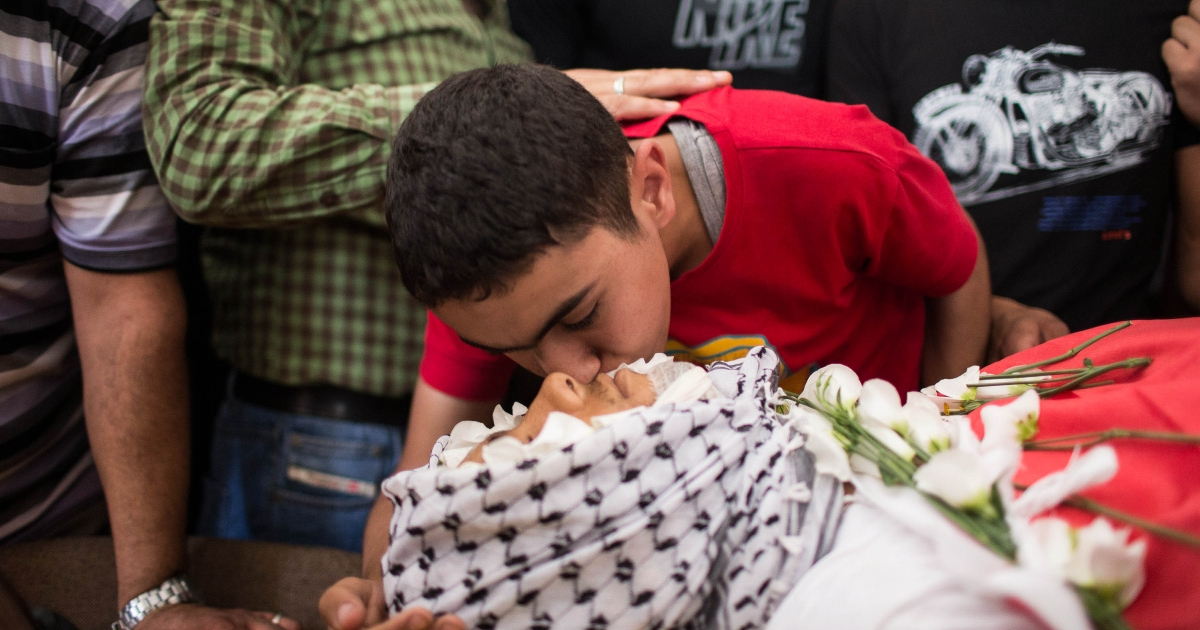 Family members kiss the corpse during the funeral held for three Palestinians killed during an Israel Defense Force operation at Kalandia refugee camp on August 26, 2013 in Ramallah, West Bank. At least 15 people were injured as Palestinians clash with undercover Israeli troops.</p>