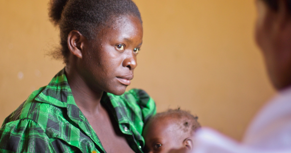 Elina Makopo, left, and her 12-month-old daughter, Jane, visit with community health worker Elizabeth Kafumo at the Kamupundu Primary Health Care Unit in Lufwanyama, Zambia.</p>