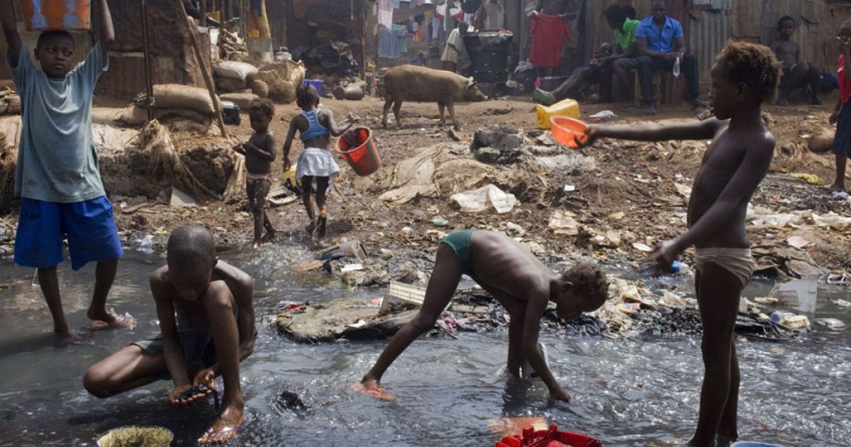 Young children retrieve anything of value from the Crocodile River in the slums of Kroo Bay in Freetown, Sierra Leone.</p>