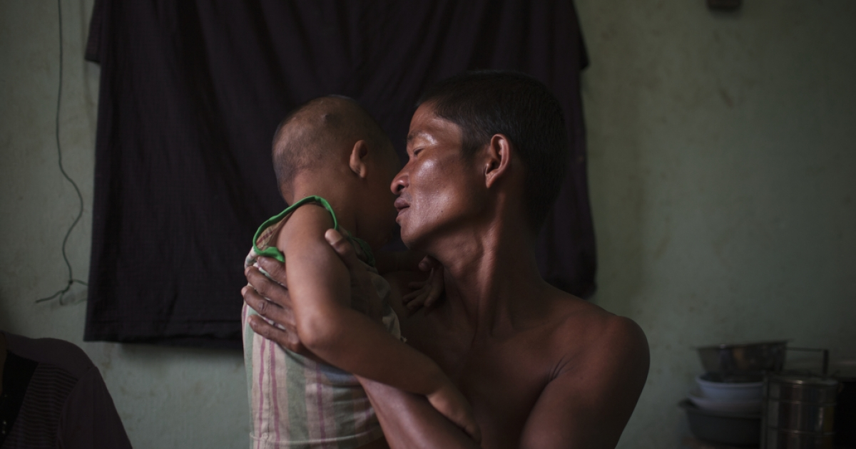 Chit Hlaing Oo, 43, holds his son, who is ill, in his home in South Dagon Township, Yangon, Myanmar. A father of 8, he has lost 4 children to disease, including a daughter three months before.</p>