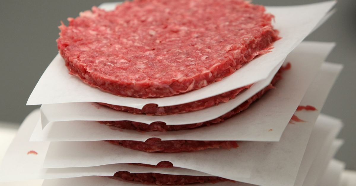 A stack of ground beef patties moves on a conveyor belt at a meat packing and distribution facility June 24, 2008 in San Francisco, California. In-virto beef created by the University of Maastricht has been successfully prepared for taste-testing.</p>