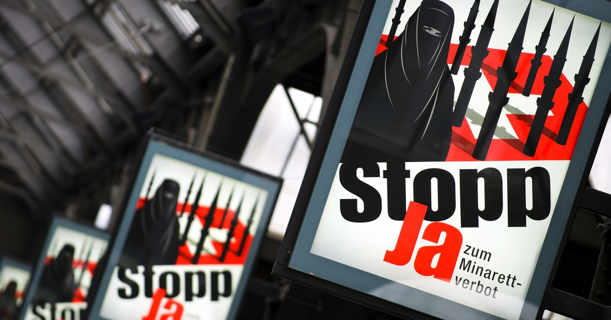 Campaign posters of the far-right Swiss People's Party depicting a woman wearing a burqa against a background of a Swiss flag upon which several minarets resembling missiles reading in German 'Stop - Yes to ban of minarets' are pictured on October 26, 2009 at the central station in Zurich. Switzerland's Commission Against Racism said that the anti-minaret poster campaign defamed the country's Muslim minority and could threaten public peace.</p>