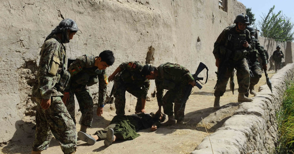 Afghanistan National Army special forces move the body of a Taliban fighter in the Gozara district of Herat province on August 30, 2013. Eight Taliban fighters including a Taliban commander were killed and one special forces soldier wounded after an early morning attack.</p>