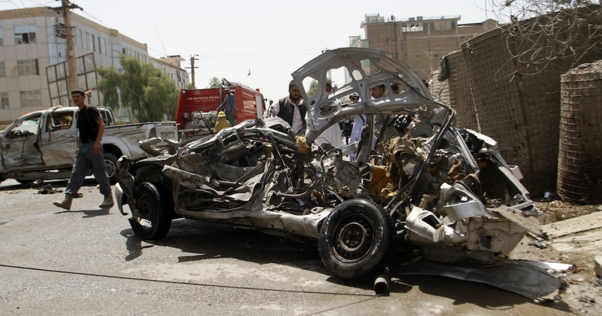 The mangled wreckage of a vehicle is seen at the site of a suicide attack in Kandahar on August 31, 2013. At least six Afghans were killed and 20 others wounded on Saturday morning after suicide attacker targeted police in southern Kandahar city, officials said.</p>