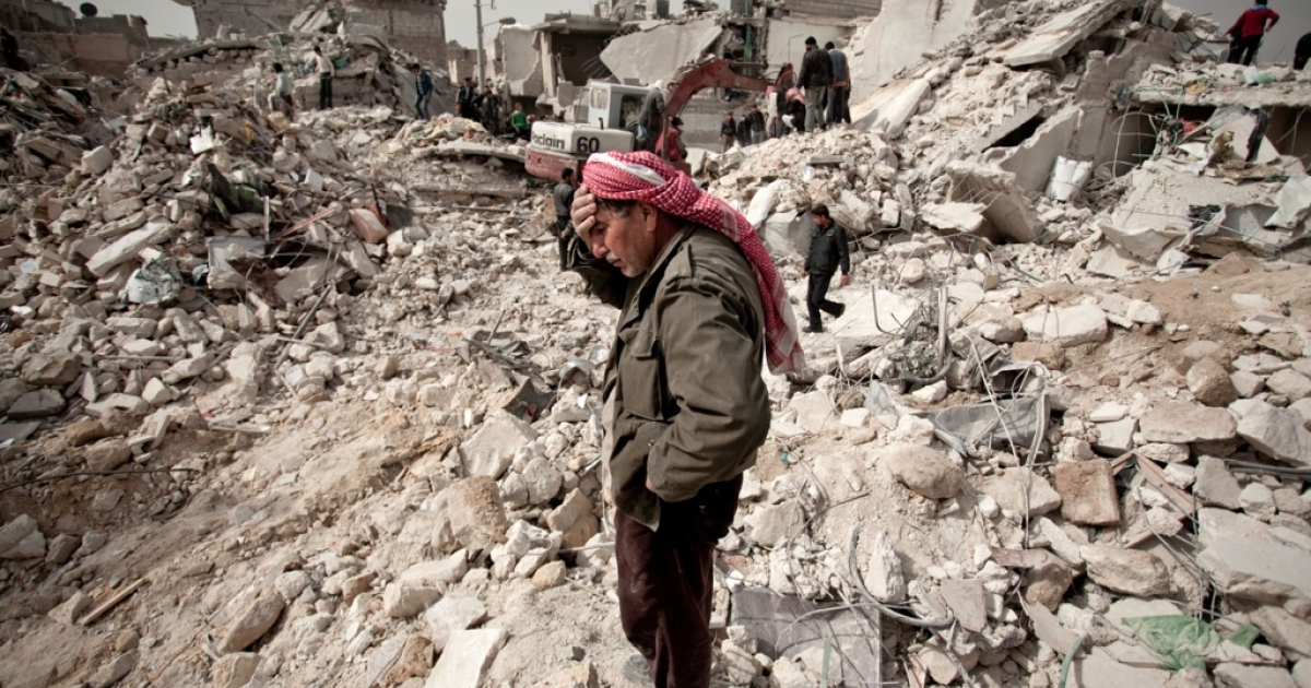 A Syrian man reacts while standing on the rubble of his house while others look for survivors and bodies in the Tariq al-Bab district of the northern city of Aleppo on February 23, 2013.</p>