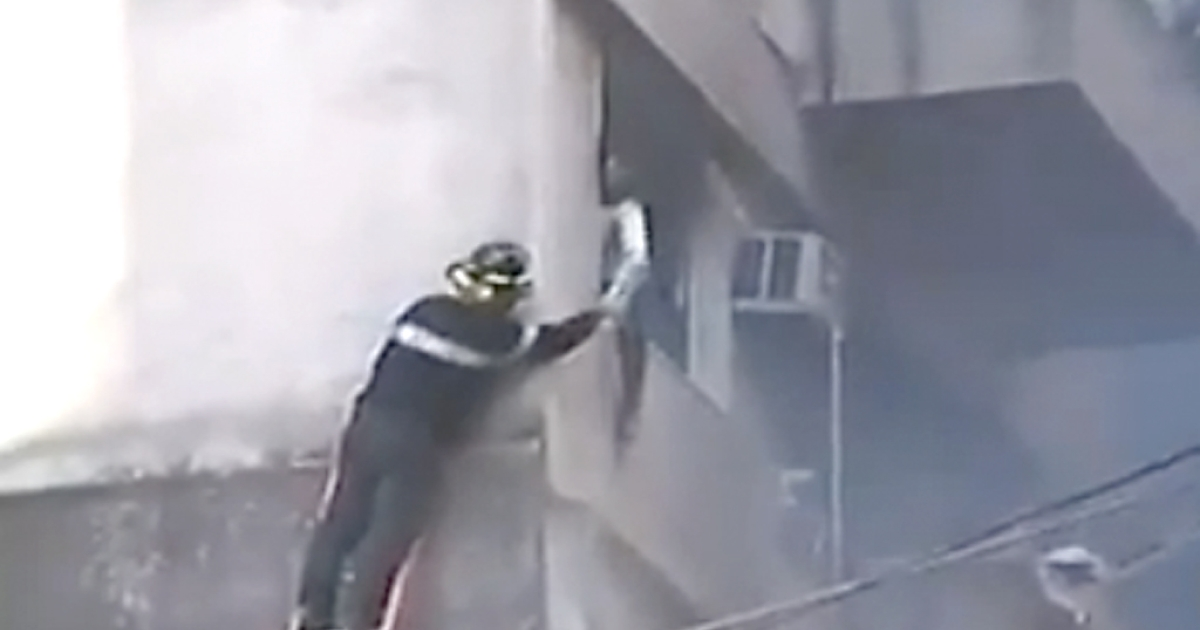A firefighter hands water to a survivor after an explosion at a downtown Rosario, Argentina, apartment building on Aug. 6, 2013.</p>