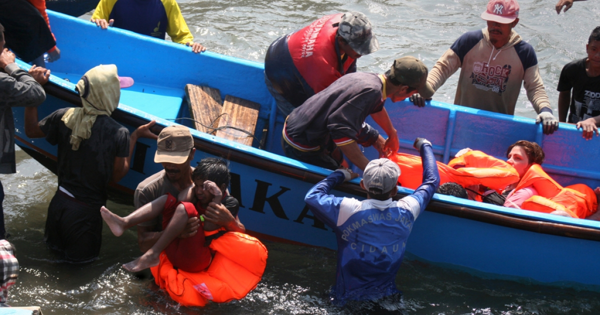 Rescuers assist survivors arriving on fishing boat at the wharf of Cidaun, West Java on July 24, 2013 after an Australia-bound boat carrying asylum-seekers sank off the Indonesian coast.</p>