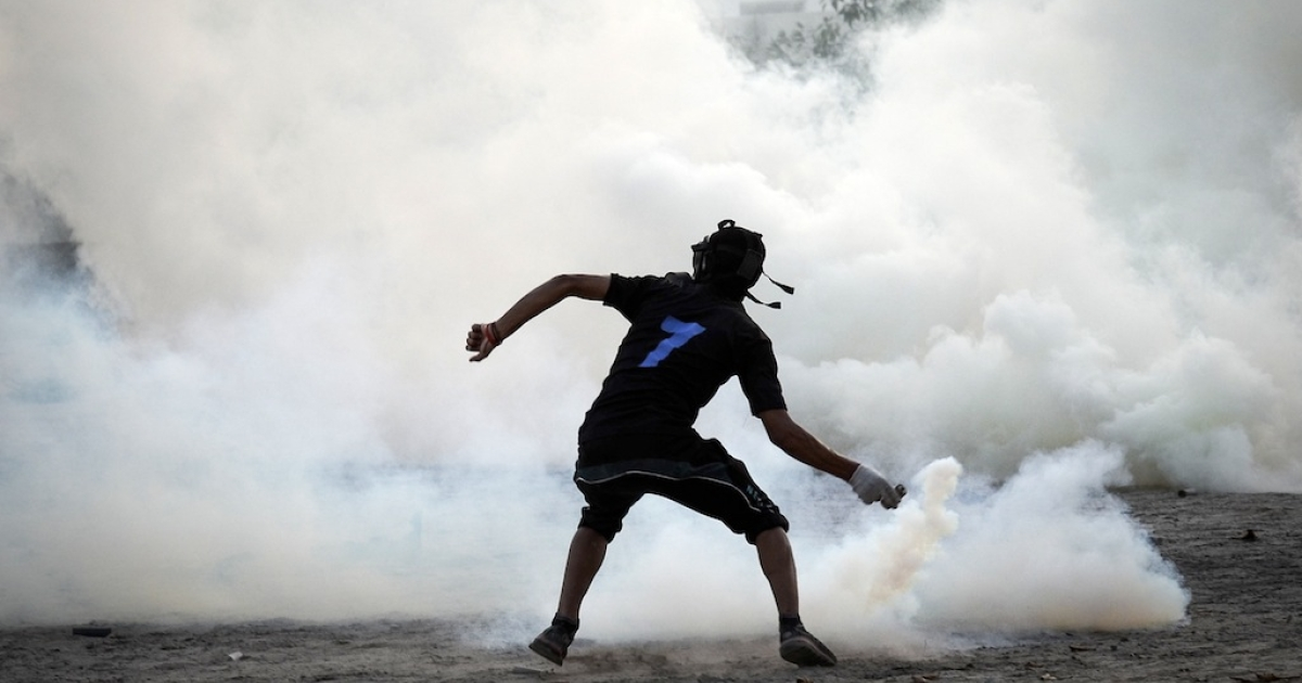 A Bahraini protestor throws back a tear gas canister fired by riot police during clashes following an anti-regime protest in the village of Abu Saiba, west of Manama, on August 15, 2013.</p>