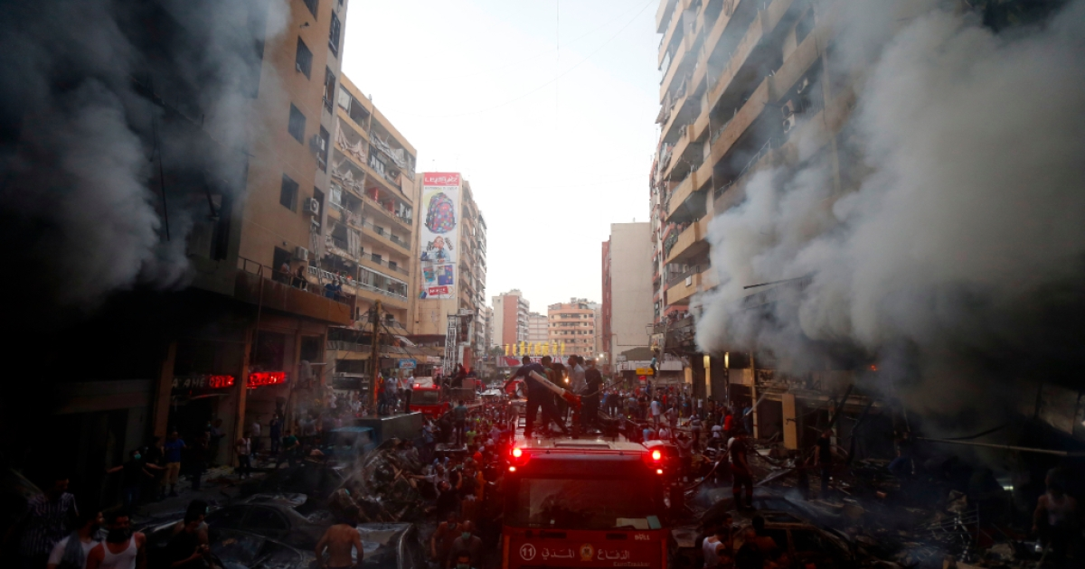 Lebanese civilians and emergency personnel gather at the site of a car bomb between the Bir el-Abed and Roueiss neighbourhoods, in the southern suburb of Beirut on August 15, 2013.</p>